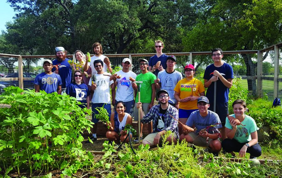 The Green Society poses with the community garden. Photo Courtesy of The Green Society
