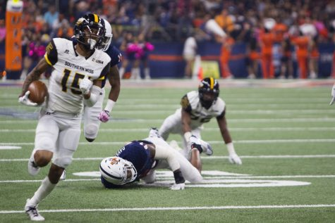 Southern Miss's Ito Smith breaks a tackle while rushing around two UTSA defenders. Chase Otero/The Paisano