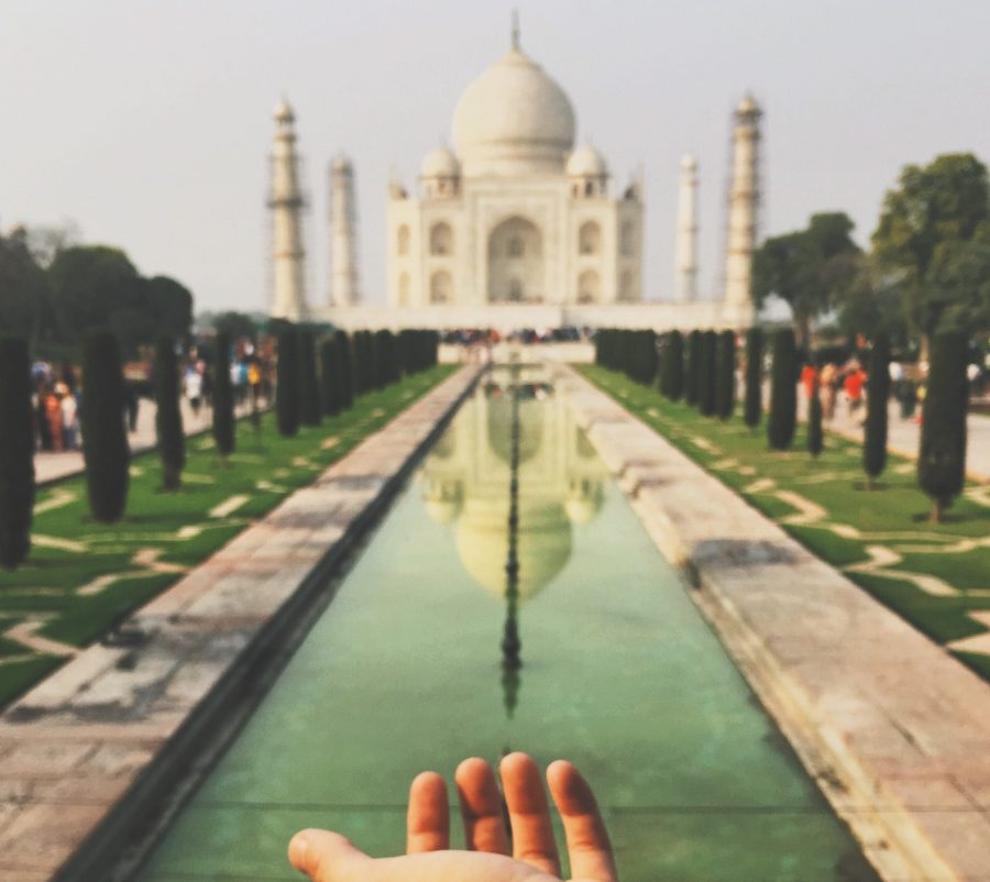 A student studying in India stretches  his hand for a photo with the Taj Mahal. Photo Courtesy of Brandon Lanners/Education Abroad Services