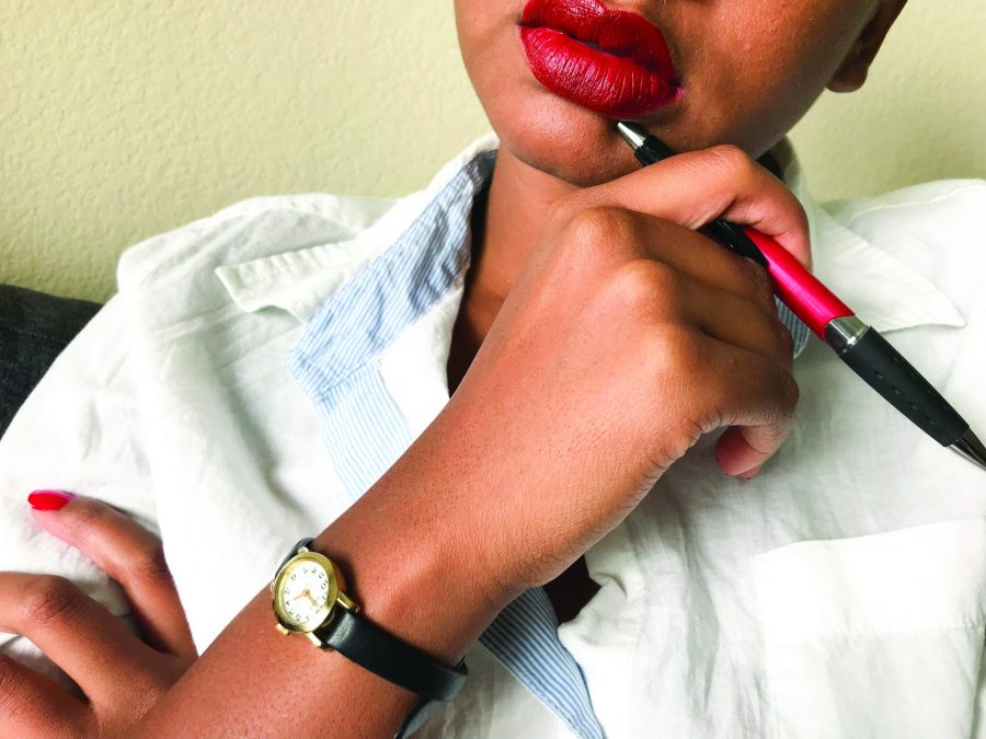 women wearing red lipstick and holding a pen