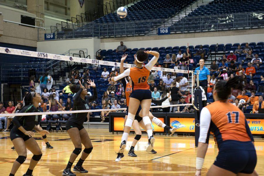 A UTSA volleyball player spiking the ball.