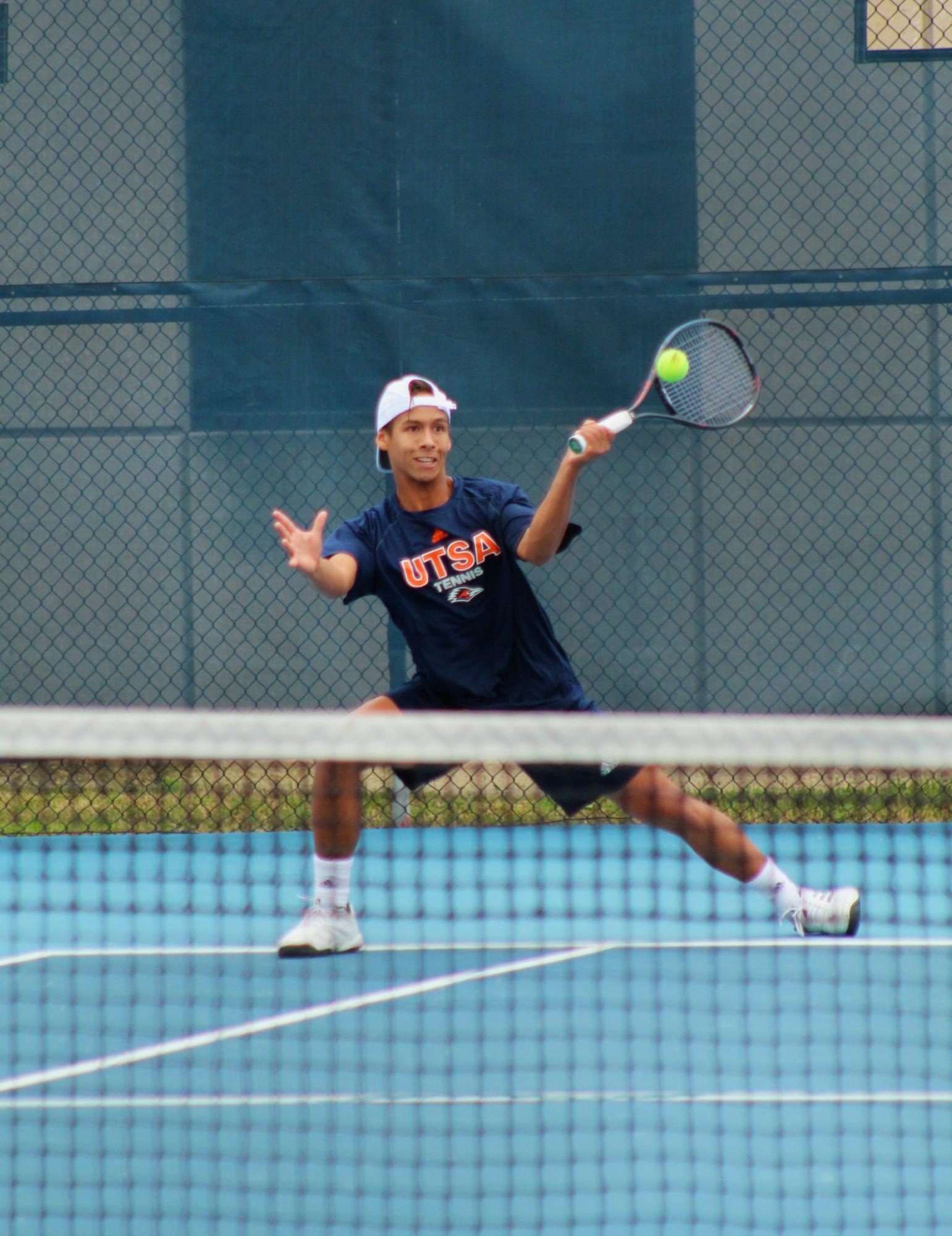 Alan Sanson volleys the ball over the net. Ethan Gullett / The Paisano