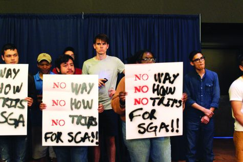 Students hold signs in protest to student government budget. Photo by Robyn Castro