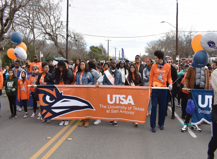Students participate in the MLK March holding a UTSA banner.