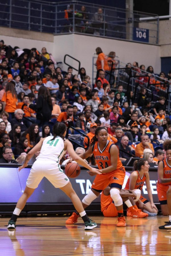 Karrington Donald attempts to pass the ball to a teammate as fans look on from the stands. It will be interesting to see how drastically the 15% attendance limit will affect crowd attendance this season.